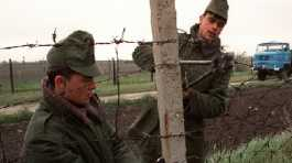 Two Hungarian soldiers using a bolt cutter to cut down a rusty barbed wire fence on the Austrian border