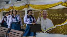 School children walk in Assumption Cathedral courtyard, decorated with posters of Pope Francis in Bangkok