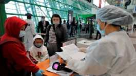 A staff member checks passengers' health certificates at the Nursultan Nazarbayev International Airport